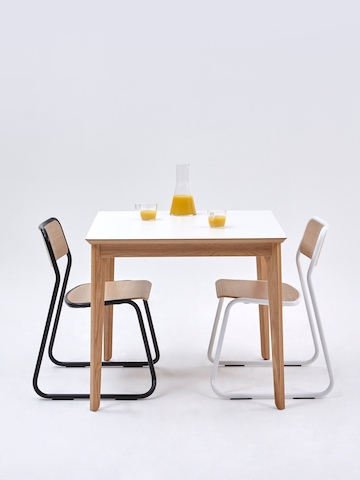 One black and one white Bounce Chair at a square white naughtone Dalby Café Table set with a carafe and two half-full glasses of orange juice.