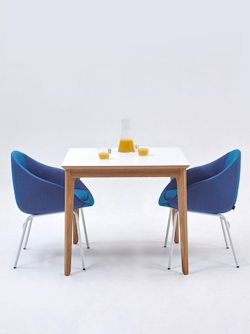 Two royal blue Always Side Chairs at a square white naughtone Dalby Café Table set with a carafe and two half-full glasses of orange juice.