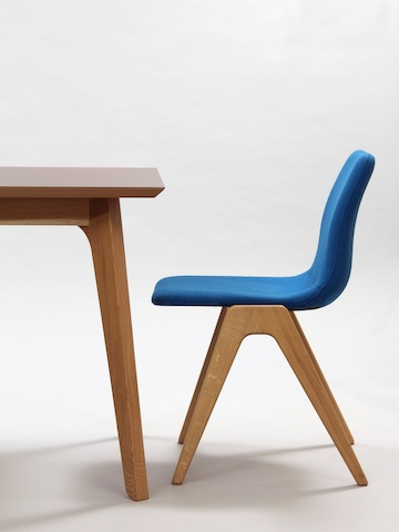 A side view of a blue Viv Wood Chair sitting at the end of a naughtone Dalby Conference Table.