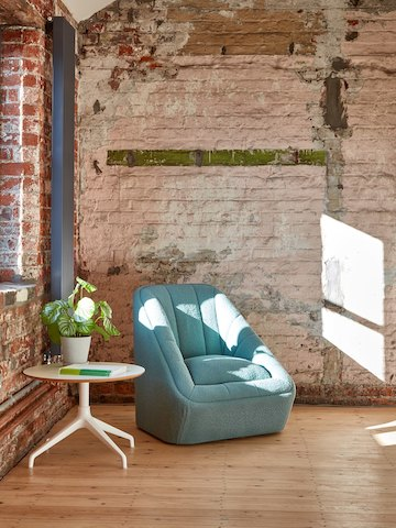 A teal naughtone Fiji Chair beside a white Ali Coffee Table adorned with magazines and a plant in a well-lit space with exposed brick walls.