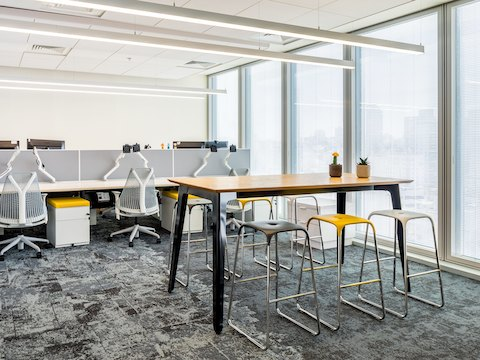 A black naughtone Fold Bar Height Table and stools in a high-rise office, a benching system and Sayl Chairs by Herman Miller in the background.