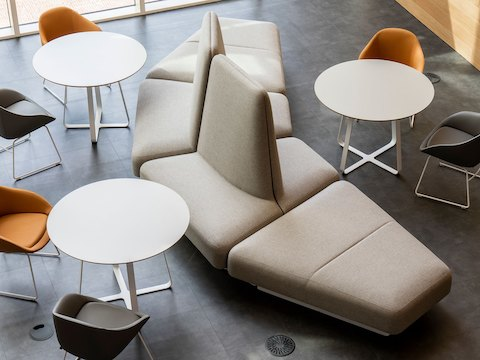 An overhead view of a beige naughtone Rhyme Modular Seating arrangement paired with three white Frog Café tables and gray and orange Always Chairs.