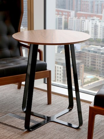A round Frog Café Table with an oak top and black base placed between two black lounge chairs near a window.