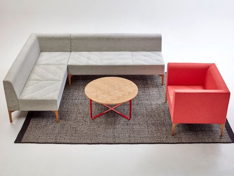 A red naughtone Hatch Lounge Chair placed in a seating arrangement with a gray Hatch Modular Seating sofa around a round Trace Coffee Table.