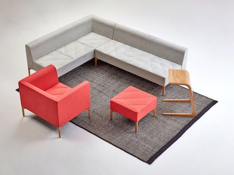A red Hatch Lounge Chair and Bench placed in a seating arrangement with a gray Hatch Modular Seating sofa, a Trace Coffee Table, and a Riley Table.