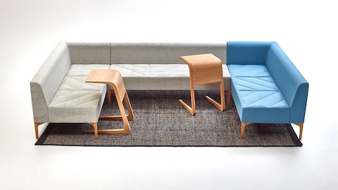 Three naughtone Hatch Modular Seating pieces - two in gray and one in blue - forming a sofa with two oak Riley Tables placed in front.