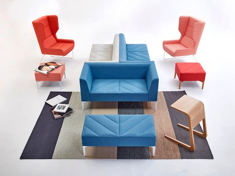 Light blue and gray Hatch Modular Seating, Sofa, and Benches along with two Hush Chairs and an oak Riley Table.