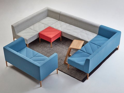 A seating arrangement made of a red Hatch Bench, light blue Sofa, and gray and blue Modular Seating pieces.