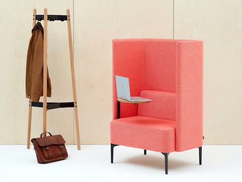 High-back Pullman Chair upholstered in pink fabric with black metal legs and oak veneer tablet arm on the righthand side. Coat stand with coat and bag.