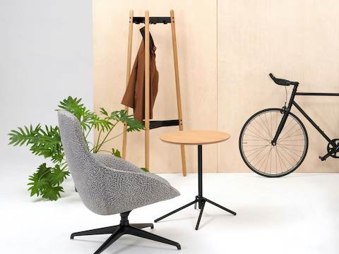 A Hudson Coat Stand with oak dowel legs and black metal supports next to an Always chair in grey, small table and bicycle.