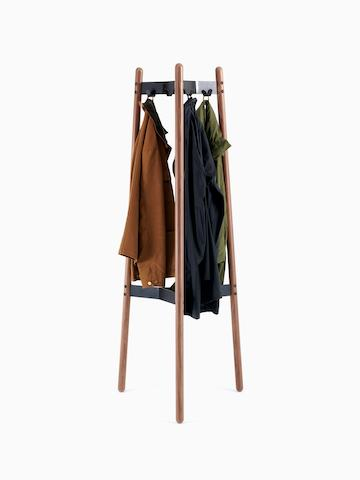 A front view of a Hudson Coat Stand with walnut dowel legs and black metal supports and coats.