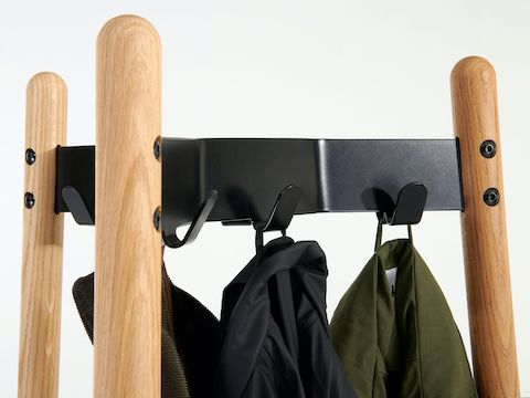Close-up view of a Hudson Coat Stand with oak dowel legs and black metal supports and coats.
