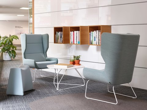 Two light blue Hush Chairs and a light blue Pinch Stool surround a Herman Miller white Polygon Wire Table in front of elevated book shelves.