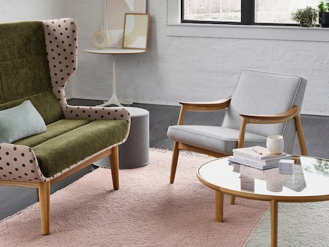 A Hush Two Seat Sofa with oak legs, a a green textile for the seat, and Maharam Dots Lychee textile exterior. The scene is set around a Port Collection Coffee Table with an oak base and glass top with a light grey high Drum Pouf, an Aspen Lounge Chair in a light grey textile, and a white Nelson Pedestal Table against a white wall.