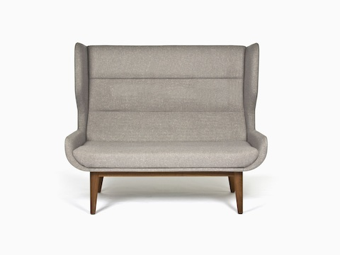 A gray, high-backed Hush Sofa with a walnut base, viewed from the front.