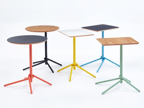 Five Knot Side Tables with two wooden tops, two black tops, and one white top. The bases are in orange, black, yellow, blue and green.
