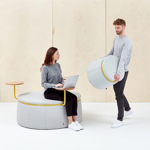 A woman sits on a three-seat Lasso Stool with tables, upholstered in pale gray fabric with yellow ring. A man walks over with a single-seat Lasso Stool.
