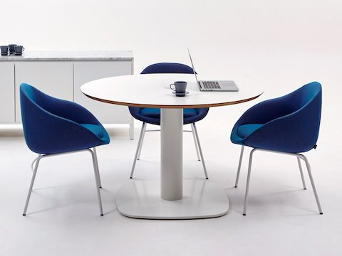 An all-white Megaped Table with three royal blue Always Lounge Chairs and a white Sideboard Storage unit in the background.