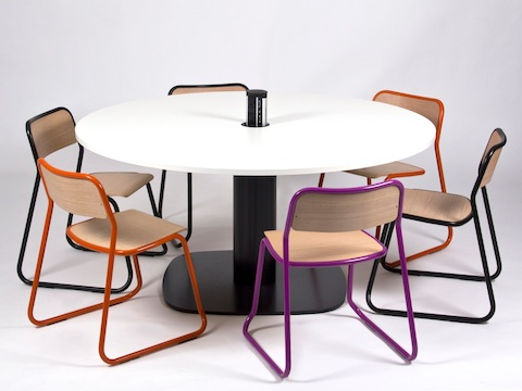 A round white naughtone Megaped Table with a black base and charging station in the centre, surrounded by orange, black and purple Bounce Chairs.