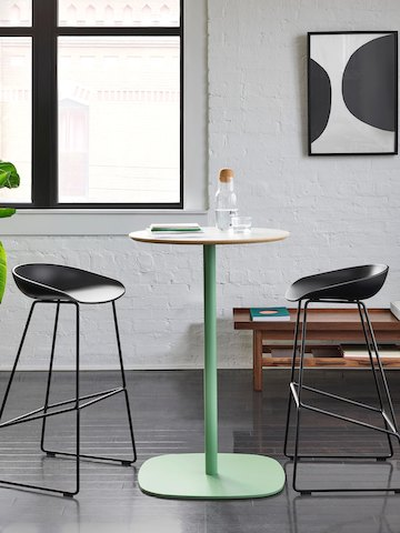 Two black About A Stool barstools around a white and pale green Ped Circular Bar Height Table. The scene is set in front of a white wall with a window, two picture frames, a green plant, and a Tamarack Table and Bench.