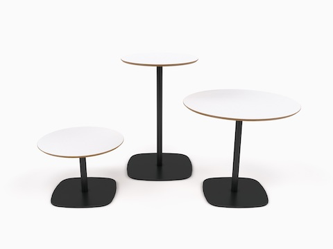 A Ped Bar Height Table between a Ped Café Table and a Ped Coffee Table, all with white tops and black bases, viewed from the front.