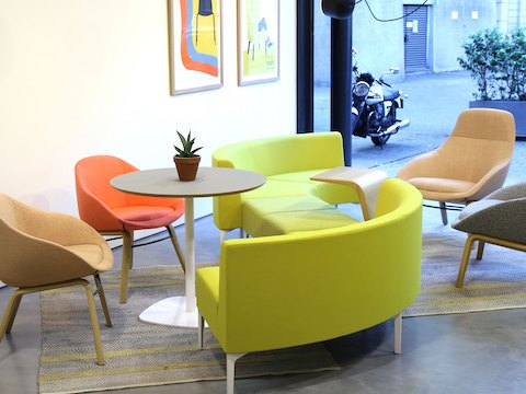 A Ped Café Table with a grey top and white base uniting two Always Lounge Chairs and a lime green Symbol Modular Seating unit.