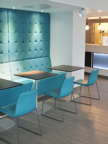 Three square walnut-topped Ped Café Tables with stainless-steel bases create a dining experience with blue Viv Side Chairs.