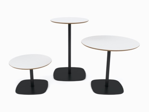 A Ped Bar-Height Table between a Ped Café Table and a Ped Coffee Table, all with white tops and black bases, viewed from the front.