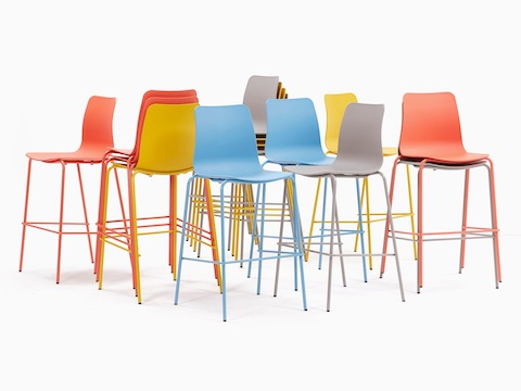 The naughtone Polly Stool family staged with numerous orange, yellow, gray, and blue stools - some stacked, facing multiple directions.