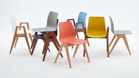 The Polly Wood Chair family with various color seats paired with oak and walnut bases facing multiple directions.