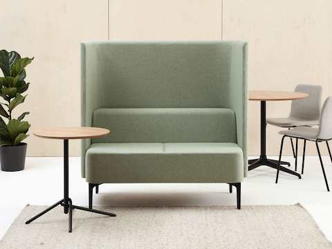 Two-seat high-back Pullman Sofa, upholstered in pale green fabric with black legs with side table and two Viv Side Chairs.