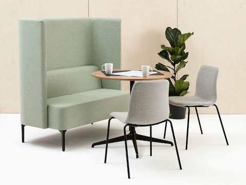 Two-seat high-back Pullman Sofa, upholstered in pale green fabric with black legs, sat with two Viv Side Chairs and a Ali Meeting Table.