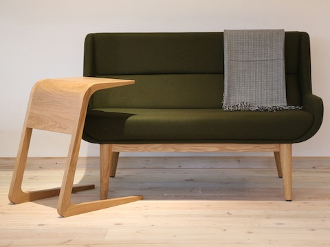 A Riley Table in oak standing alongside a dark green naughtone Hush Sofa.