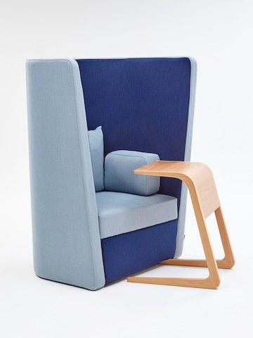 A naughtone Busby Chair, upholstered in light and dark blue, viewed at an angle beside an oak Riley Table.