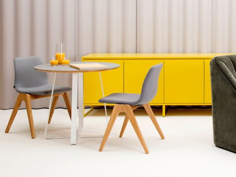 A yellow Sideboard Storage unit staged behind two grey Viv Wood Chairs and a white Frog Café Table.