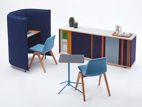 A full navy Softbox Storage Credenza with colorful stripes opened partially and arranged with a Cloud 1.5 Desk, Viv Wood Chairs, and a Knot Table.