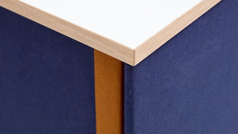 A close-up view of the corner of a navy naughtone Softbox Storage Credenza with a dark orange stripe down the side.