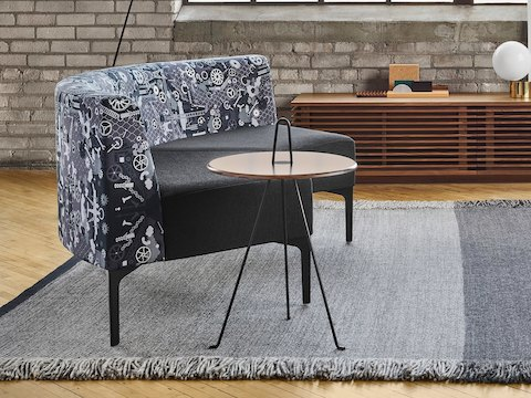 Two Symbol 90 Degree Curve Seats in a Maharam Industry fabric around two Tipi Side Tables. The scene is set on a grey rug in front of a brick wall with large windows. The space is also furnished with a Line Media Console in walnut, a black Mantis BS1 B Floor Lamp, and various other accessories.