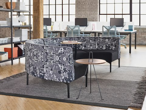 A Symbol 90 Degree Curve Seat in Maharam Industry textile next to a walnut Plex Table with a black base and a Tipi Side Table with a wood top and metal base. The scene is set on top of a grey rug and adjacent to a black Steelwood Shelving System. In the background are workstations and large windows on a brick wall.