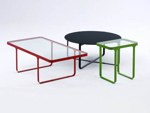 The small naughtone Trace Table family featuring a red Trace Coffee Table, a green Trace Side Table, and an all black round Trace Coffee Table.