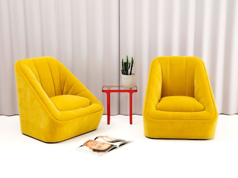 A red naughtone Trace Side Table with glass top holding a small cactus standing between two yellow naughtone Fiji Chairs with a curtain backdrop.