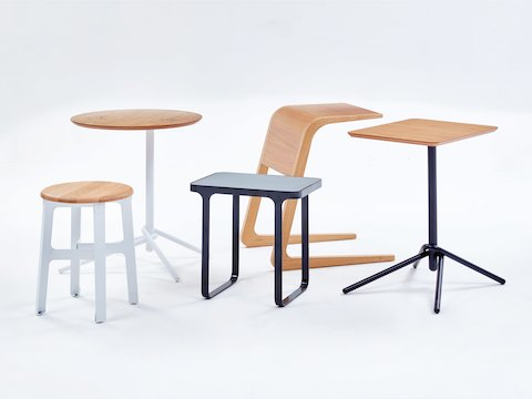 An all black naughtone Trace Side Table surrounded by naughtone wooden tables: Riley and Knot, and a Construct Stool.