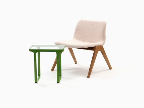 A green naughtone Trace Side Table with glass top paired with a light pink Viv Wood Lounge Chair.