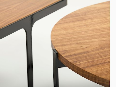 A close-up view of a round naughtone Trace Coffee Table and a Trace Table - both with wooden tops and black, metal bases.