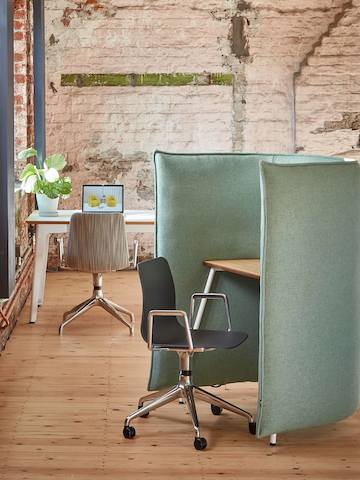A dark gray naughtone Viv Chair with metal armrests and 5-star base pulled up to a light green Cloud 1.5 Desk.