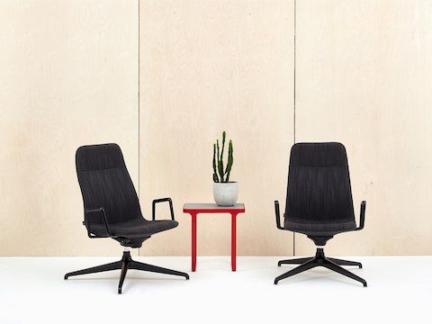Two Viv High-Back Lounge Armchairs, upholstered in black fabric with black 4-star base and red Trace Side Table.
