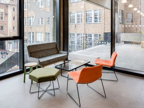 Two orange suede naughtone Viv Lounge Chairs with black sled bases arranged with various naughtone products, located in a corner of wall windows.