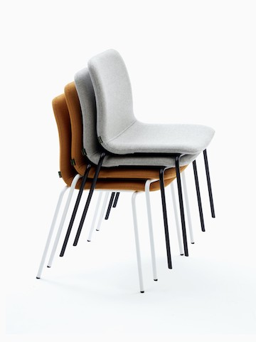 Stack of upholstered Viv Side Chairs with black and white 4-leg bases.