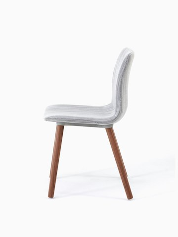 A side view of a Viv side chair upholstered in light grey fabric on walnut dowel base.