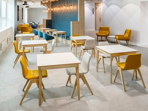 A yellow and a white naughtone Viv Wood Chair stationed at a square Dalby Café Table. Multiple arrangements of this fill an empty café.